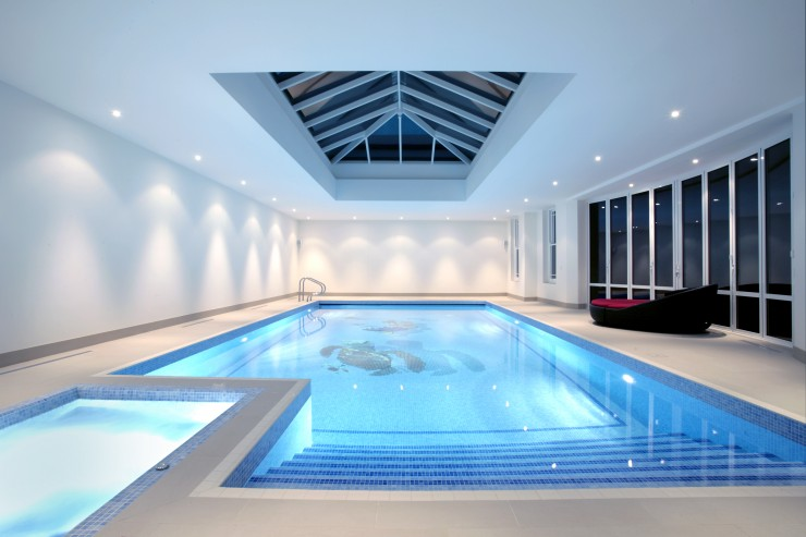 indoor pool with skylight and attached spa