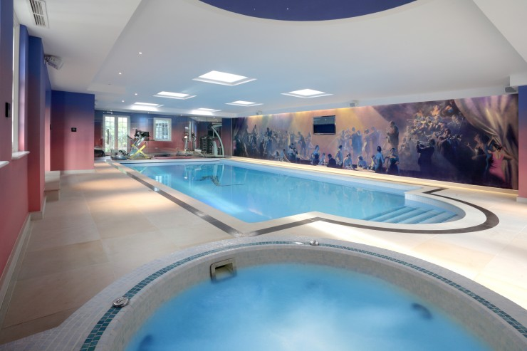 indoor pool with mural and spa